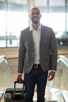 Smiling businessman standing with luggage on escalator #413615