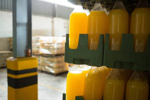 Yellow juice bottles in crate at warehouse #413627