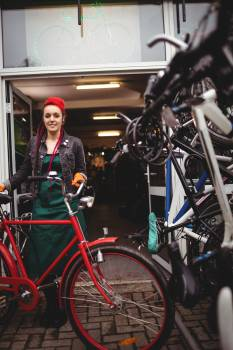 Smiling mechanic standing with a bicycle in workshop Free Photo