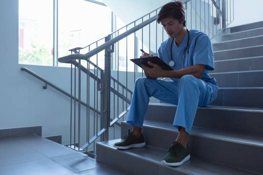 Male surgeon writing on clipboard while sitting on stairs at hospital #413665