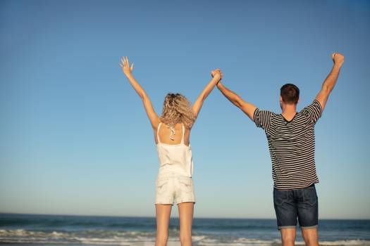 Couple standing together with arms up on the beach #413684