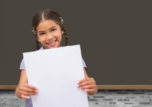 School girl holding blank paper against blackboard in background #413703