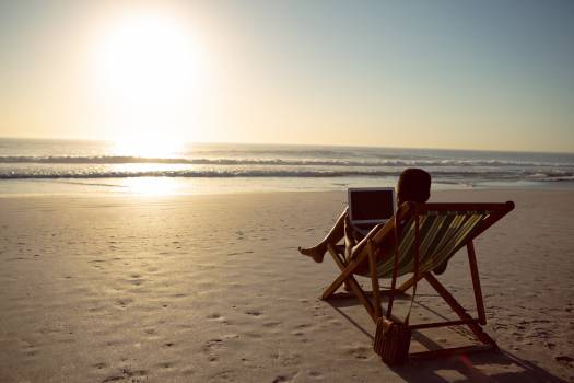 Woman using laptop while relaxing in a beach chair on the beach #413709