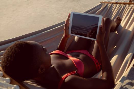 Woman using digital tablet while relaxing in a hammock on the beach #413710