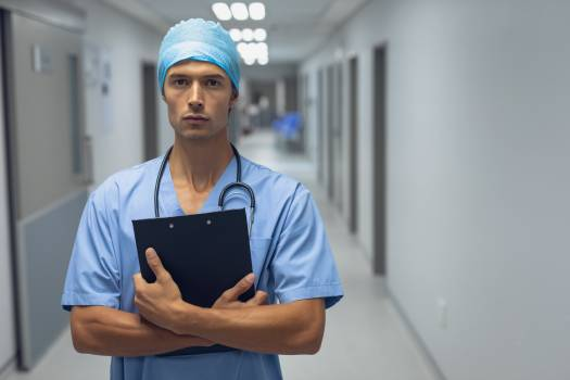 Male surgeon holding a clipboard in the corridor at hospital #413713