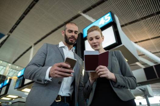 Business people holding boarding pass and using mobile phone Free Photo