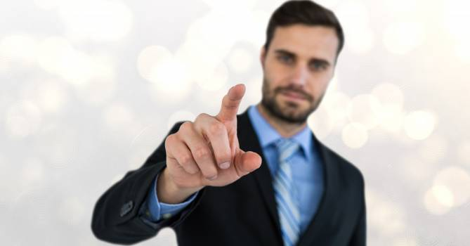 Confident businessman touching screen Free Photo