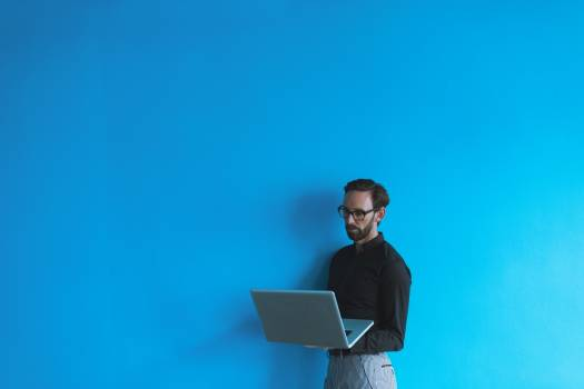 Male executive using laptop against blue wall Free Photo
