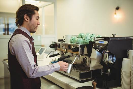 Man preparing coffee in coffee machine Free Photo