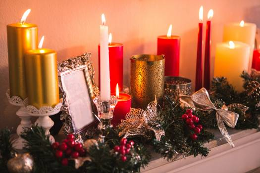 Candles and christmas decorations arranged on fireplace #413780