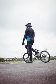 Cyclist standing with BMX bike at starting ramp #413807