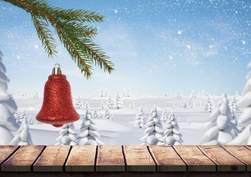 Christmas bell hanging on branch of fir tree over wooden plank with snow covered trees in background #413820