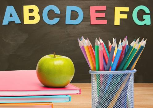 Green apple on books and colour pencils in classroom with alphabets on blackboard #413842