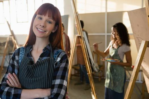 Portrait of smiling woman with arms crossed with friends painting in background #413845
