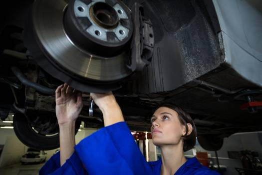 Female mechanic fixing a car wheel disc brake #413864
