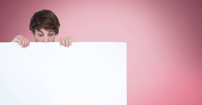 Surprised man looking at blank billboard while standing against pink background #413868