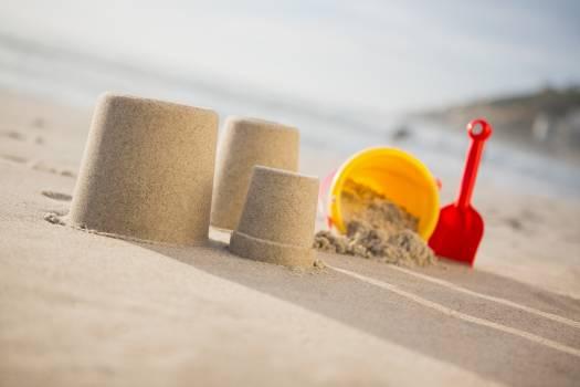Bucket, spade and sand castles on beach Free Photo