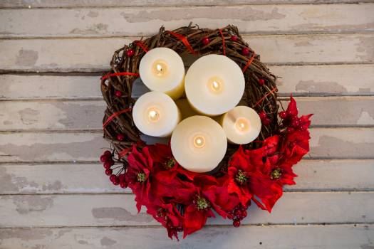 Candles decorated with flowers nest basket on wooden plank #413878