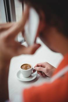 Man talking on mobile phone while having coffee #413910
