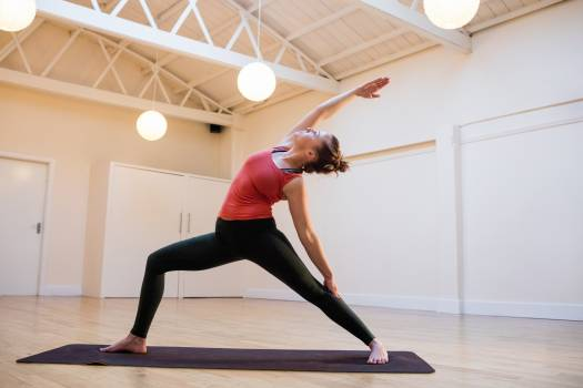 Woman performing extended side angle pose on exercise mat #413919