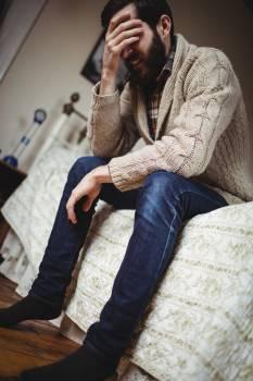 Depressed man sitting on bed Free Photo