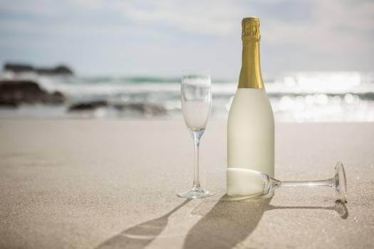 Champagne bottle and two glasses on sand #413954