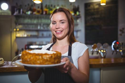 Portrait of waitress holding a plate of cake #413957