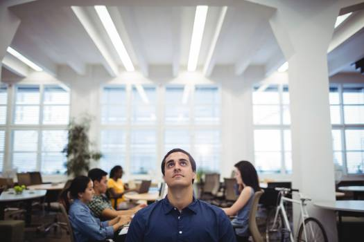 Man looking up while colleagues working in background Free Photo