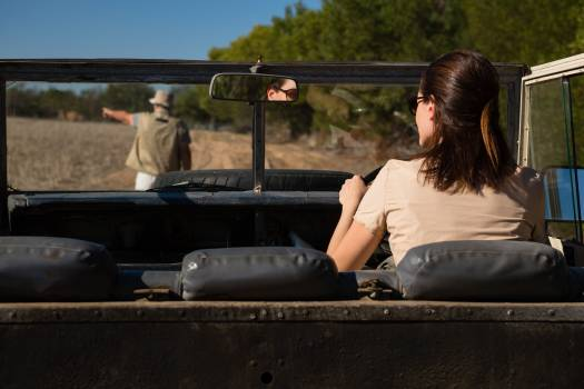 Rear view of man seen through windshield with woman driving vehicle Free Photo