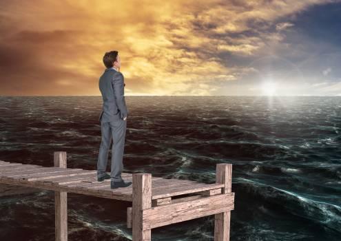 Thoughtful businessman standing on wooden bridge in sea #414055