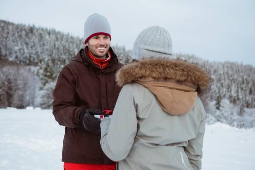 Woman giving gift to man on snow covered mountain #414060