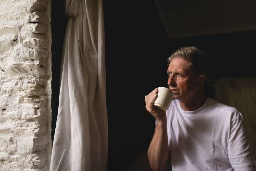 Senior man having coffee near window at home #414090