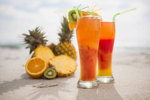 Two glasses of cocktail drink and tropical fruits kept on sand #414114