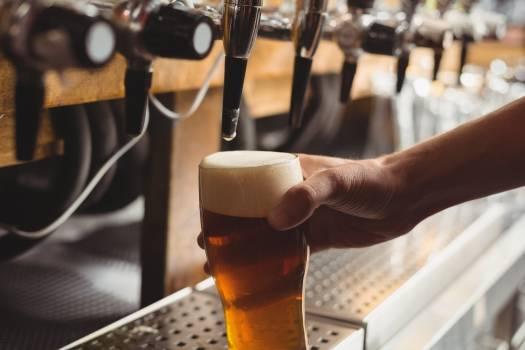 Close-up of bar tender filling beer from bar pump #414131