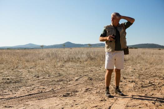 Man with binocular looking away while standing on landscape #414153