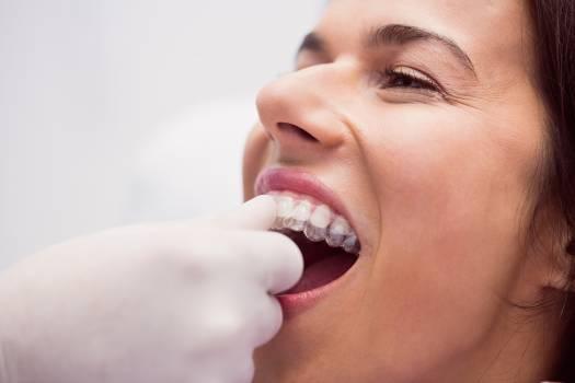 Dentist assisting female patient to wear braces #414164