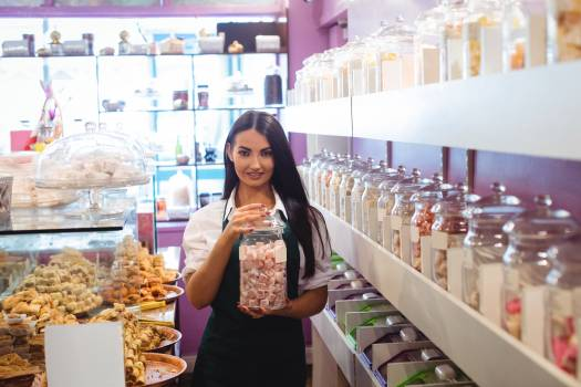 Portrait of female shopkeeper holding jar of turkish sweets at counter #414170