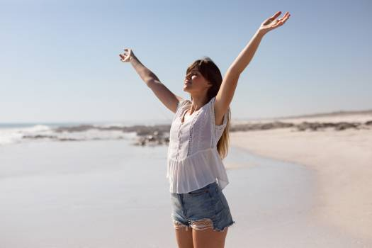 Beautiful woman with arms stretched out standing on beach in the sunshine #414173