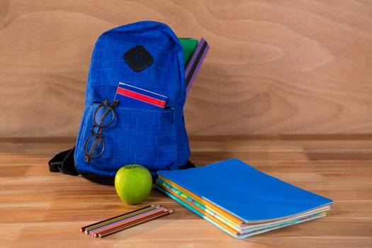 Close-up of school bag with books and stationery Free Photo
