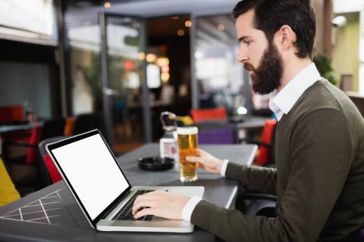 Man using laptop while having glass of beer #414210