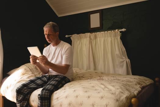 Senior man using digital tablet in bedroom #414211