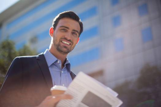 Smiling businessman holding newspaper and coffee cup near office building #414215