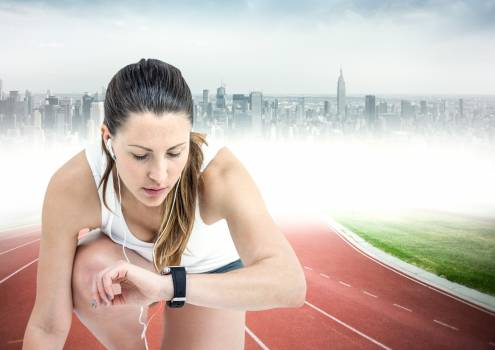 Female runner with headphones on track against blurry skyline #414239
