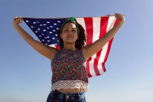 Beautiful young woman waving american flag on beach in the sunshine #414250