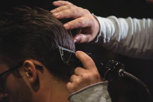 Close-up of man getting his hair trimmed with trimmer Free Photo