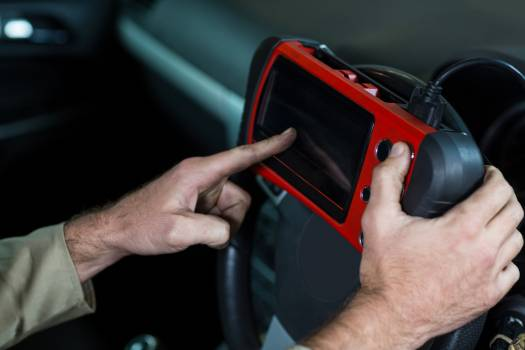 Mechanic using a diagnostic tool #414329