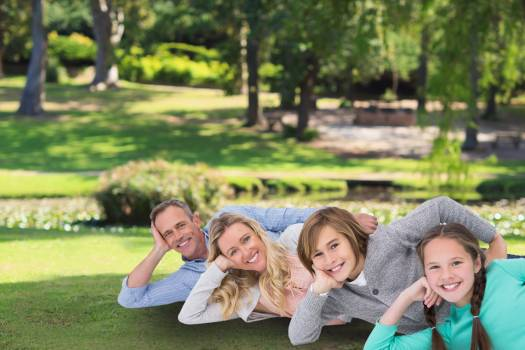 family laying on the grass Free Photo