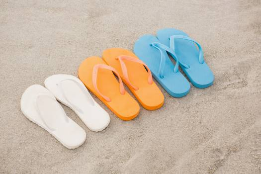 Multi-color flip flops arranged in a row in sand #414356