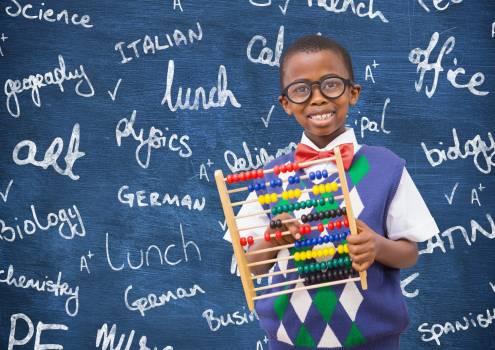 Intelligent schoolboy holding abacus Free Photo