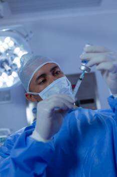 Male surgeon filling medicine from ampule into syringe in operation room at the hospital #414368